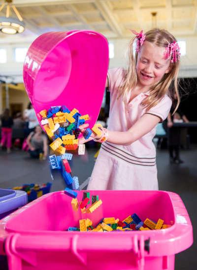 girl pouring lego blocks into a bucket
