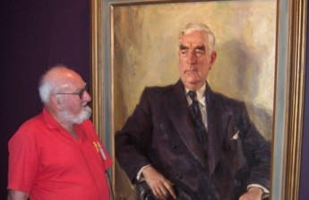 Frank Jennings with the portrait of Prime Minister Sir Robert Menzies at the Museum of Australian Democracy