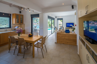 Open kitchen extending into the living room, terrace and pool