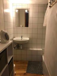 Petite salle de douche avec lavabo et rangement