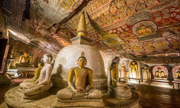 Im Kreis angeordnete Buddha-Statuen und verzierte Gewölbe im Goldenen Höhlentempel von Dambulla in Sri Lanka