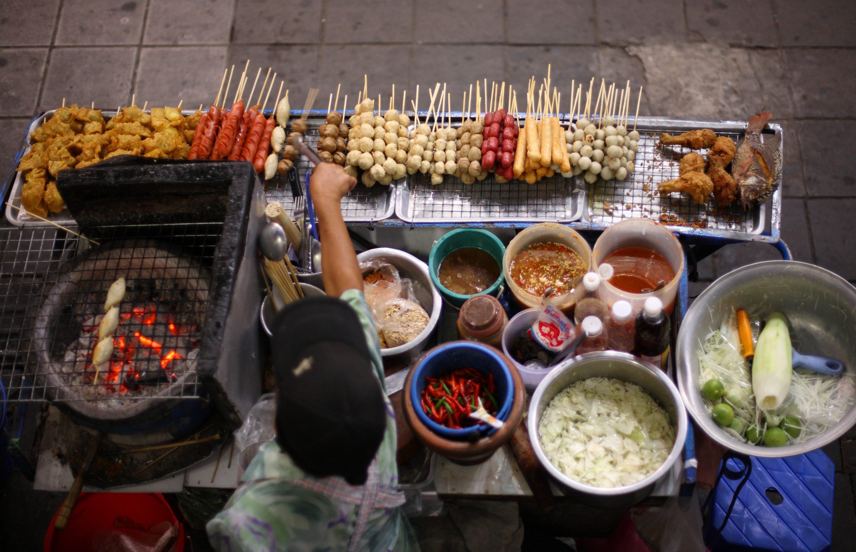 Verkäufer eines Straßenstandes bereitet thailändische Spezialitäten zu