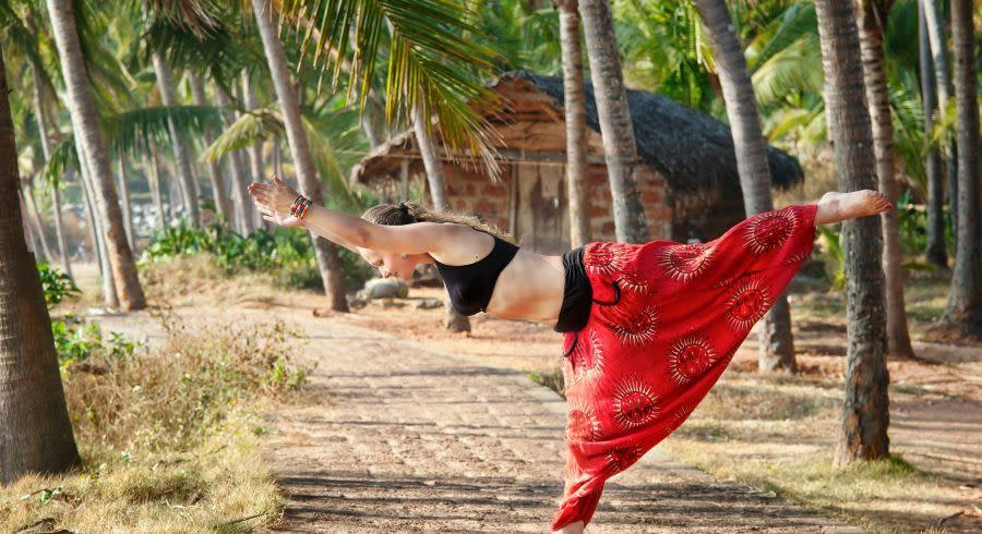 Yoga virabhadrasana warrior pose by beautiful Caucasian woman, India, Kerala, Varkala, Asia