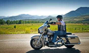 a man sitting on a motorcycle in front of a mountain