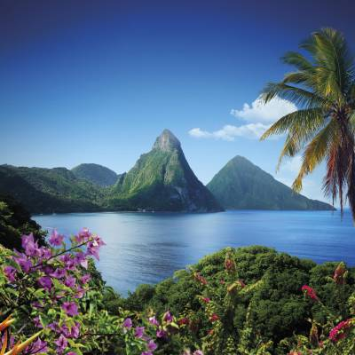a large body of water surrounded by trees with Pitons in the background