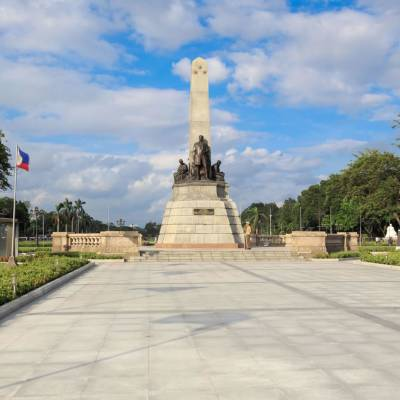 a large red kite in the sky with Rizal Park in the background