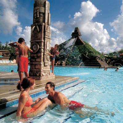 a group of people swimming in a pool of water with Disney's Coronado Springs Resort in the background