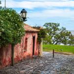 Verwittertes rotes Häuschen, Kopfsteinpflaster und alte Laternen in Uruguay