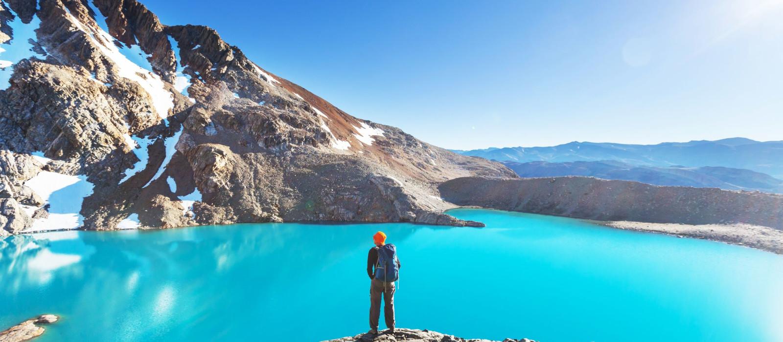 Wanderer blickt auf türkisblauen Gletschersee in Patagonien