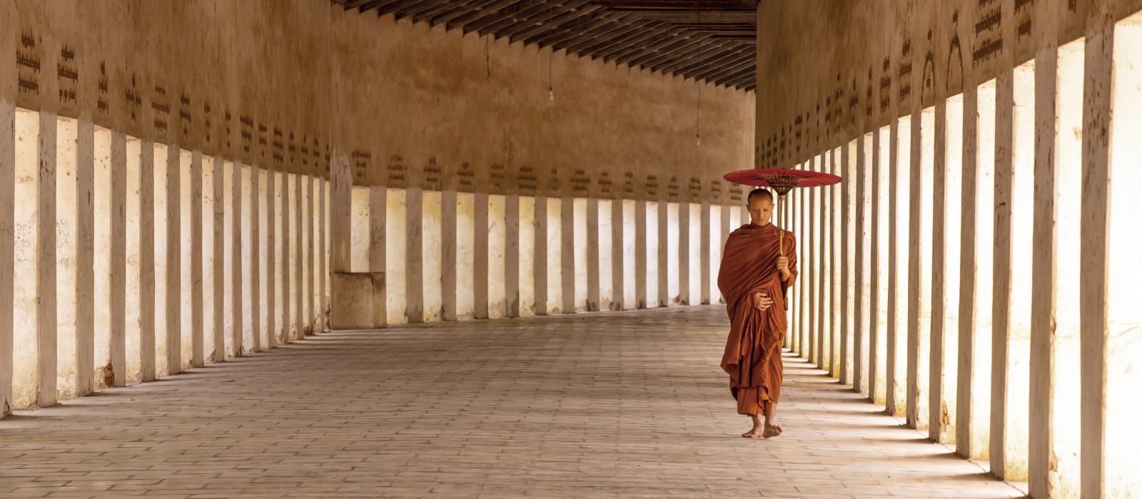 Mönche kommen, um den alten Buddha in der buddhistischen Pagode in Bagan, Myanmar, zu besuchen und zu respektieren, mit einem Regenschirm, der den Hintergrund des Sonnenlichts hält.