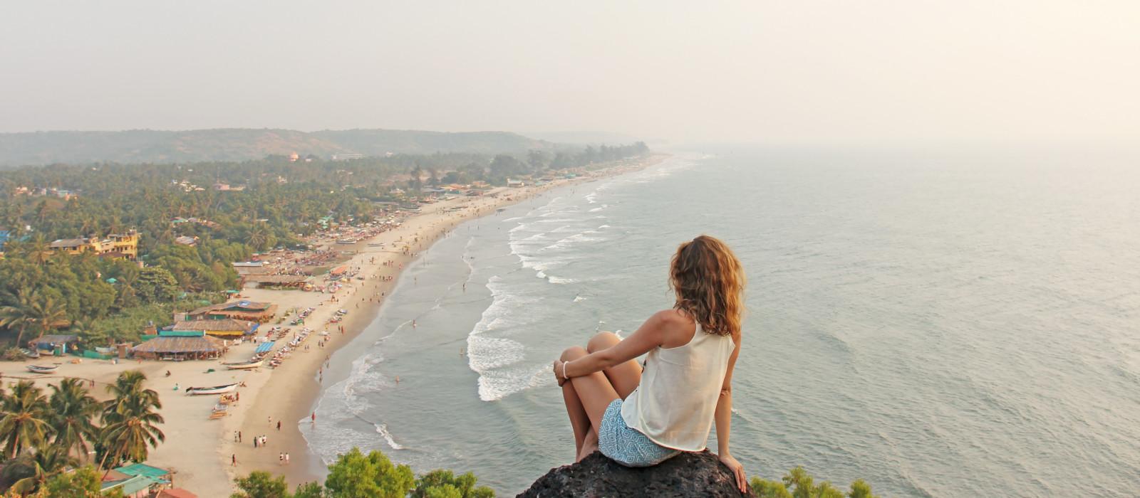 Ein junges Mädchen mit blonden Haaren sitzt auf einem Berg und schaut auf das Meer und den Strand, Arambol, Goa, Indien