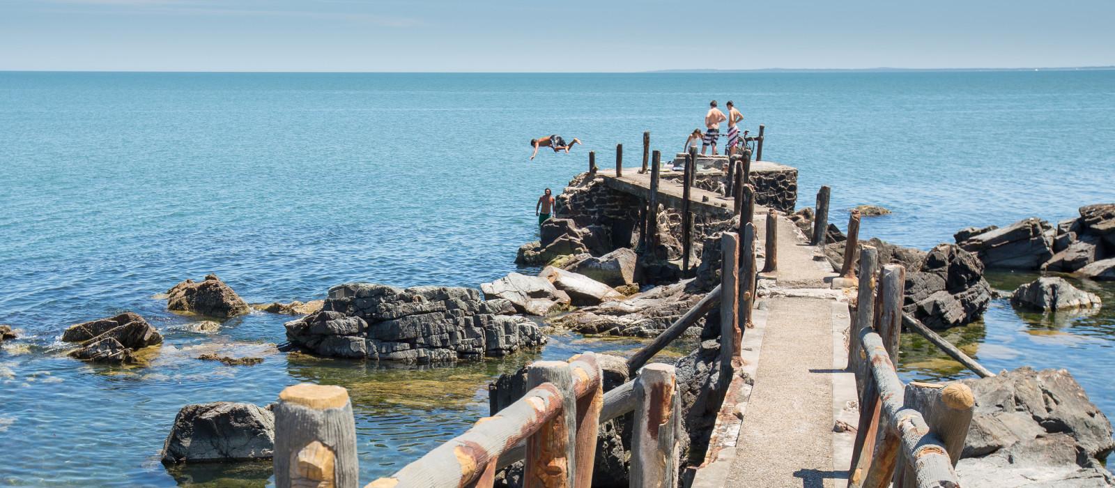 Schwimmer springen vom Steg in den Rio de la Plata, Uruguay