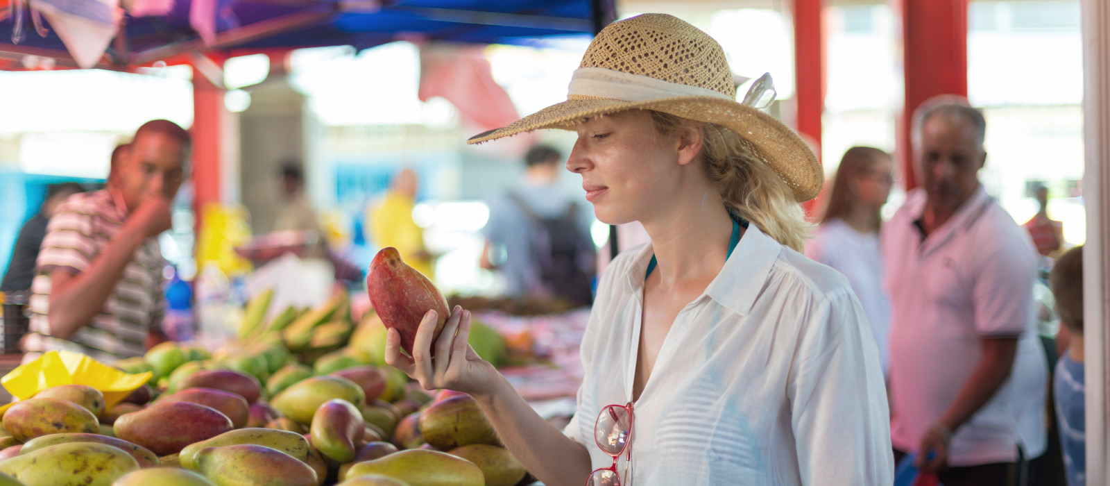 Female traveler wearing elegant colonial style white tunic and hat buying fresh tropical fruit on traditional Victoria food market on Seychelles islands