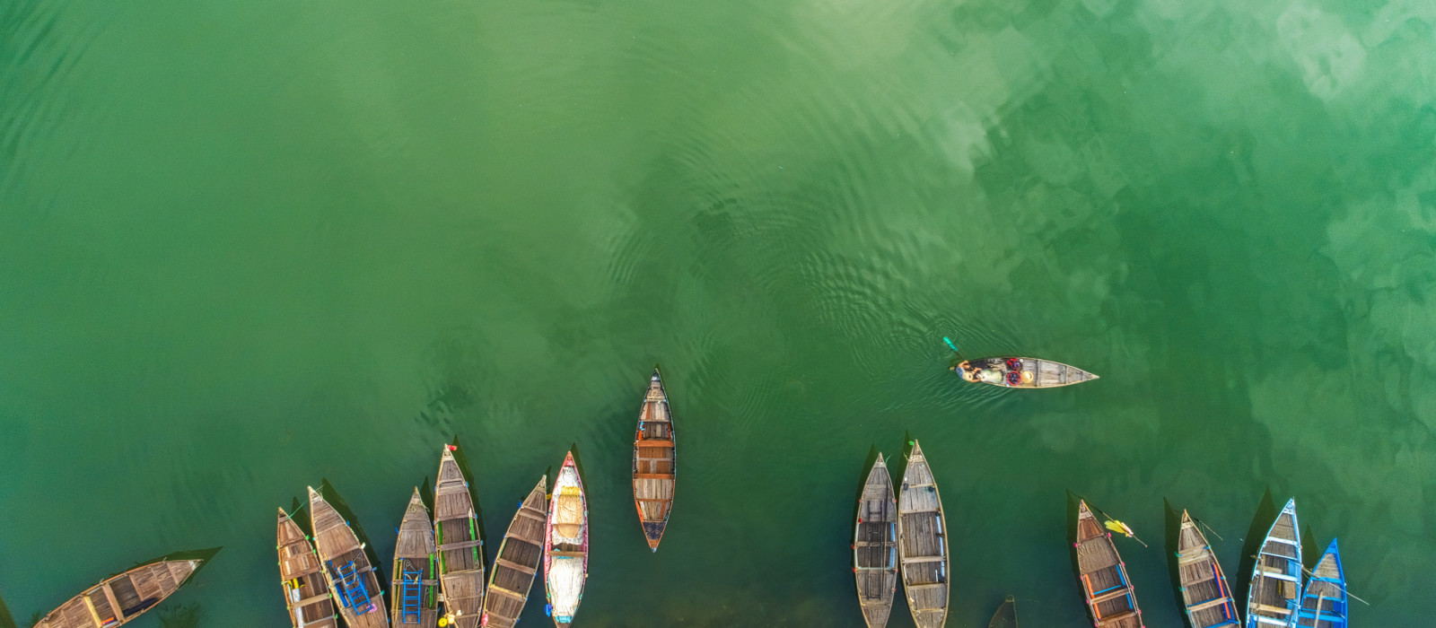 Aerial view or Top view of beautiful clear sea water with colorful long tail boats in the summer of tropical island