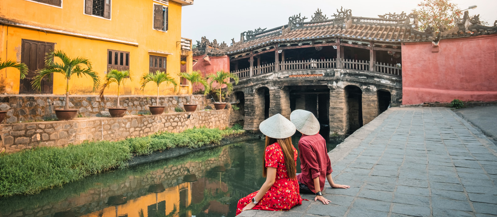 Travel couple with Japanese Covered Bridge, in Hoi An, Vietnam, Asia