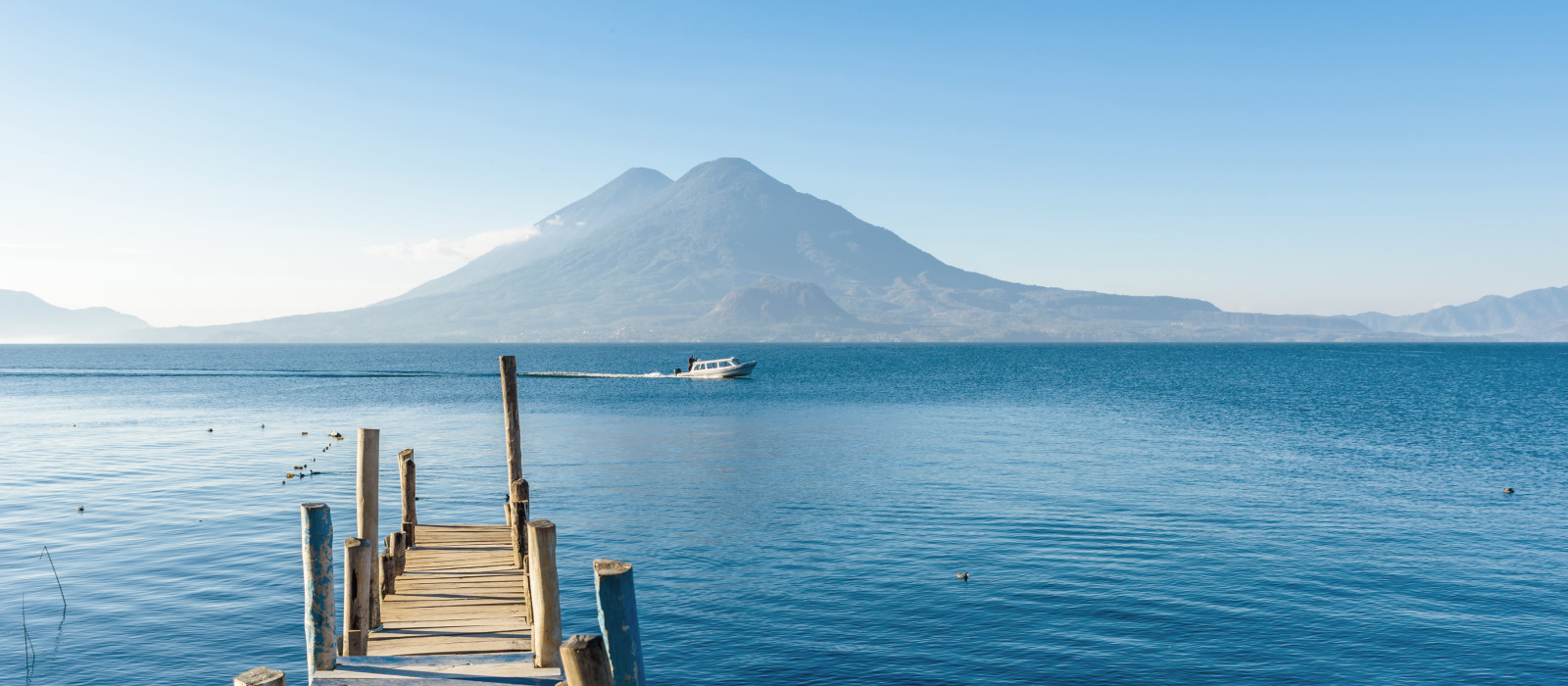 Wooden jetty on Lake Atitlan on the shore in Panajachel, Guatemala. With beautiful landscape of volcanoes landscape