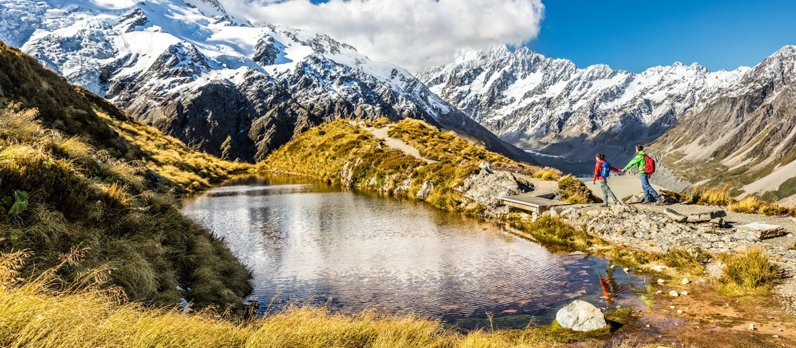 Hiking travel nature hikers in New Zealand. Couple people walking on Sealy Tarns hike trail route with Mount Cook landscape, famous tourist attraction - New Zealand travel