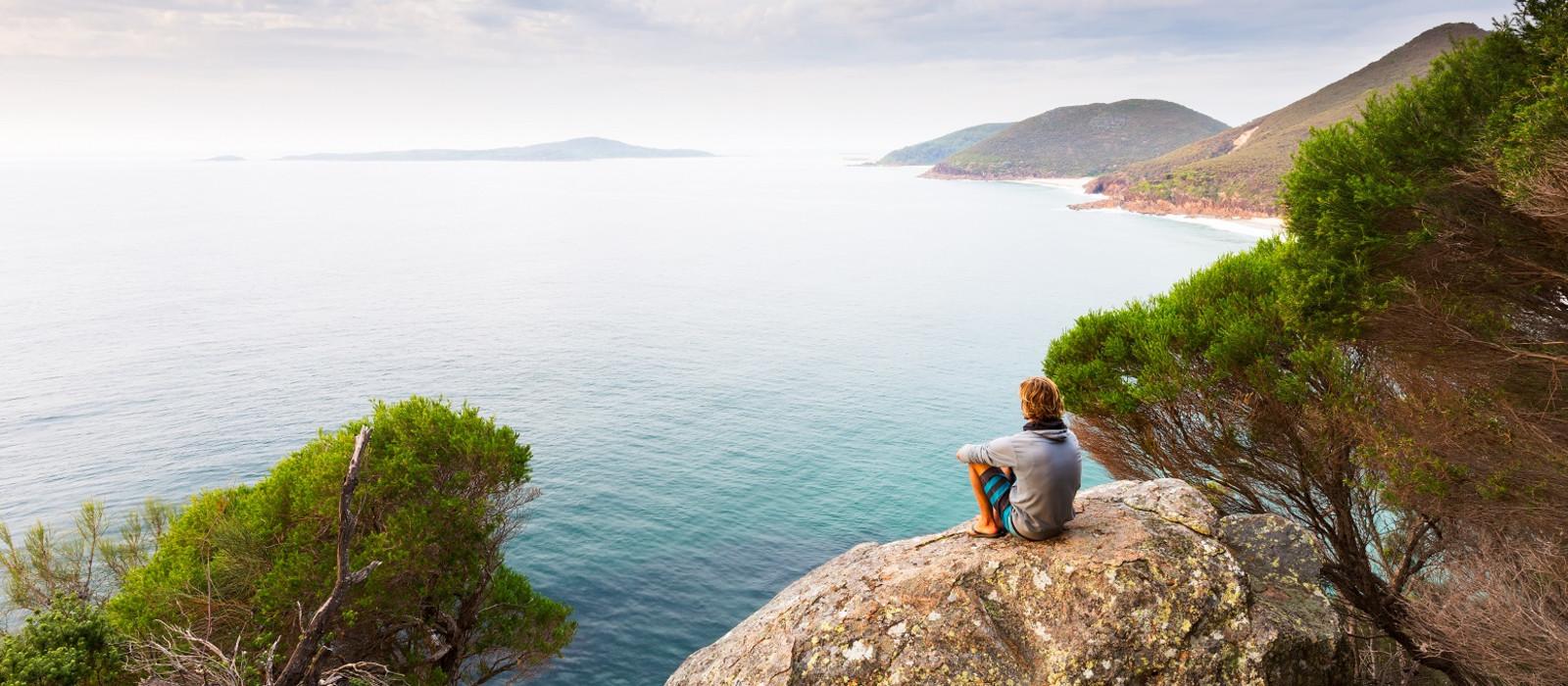 Junger Mann sitzt auf einem Felsen mit Blick Wasser in Newcastle, Australien