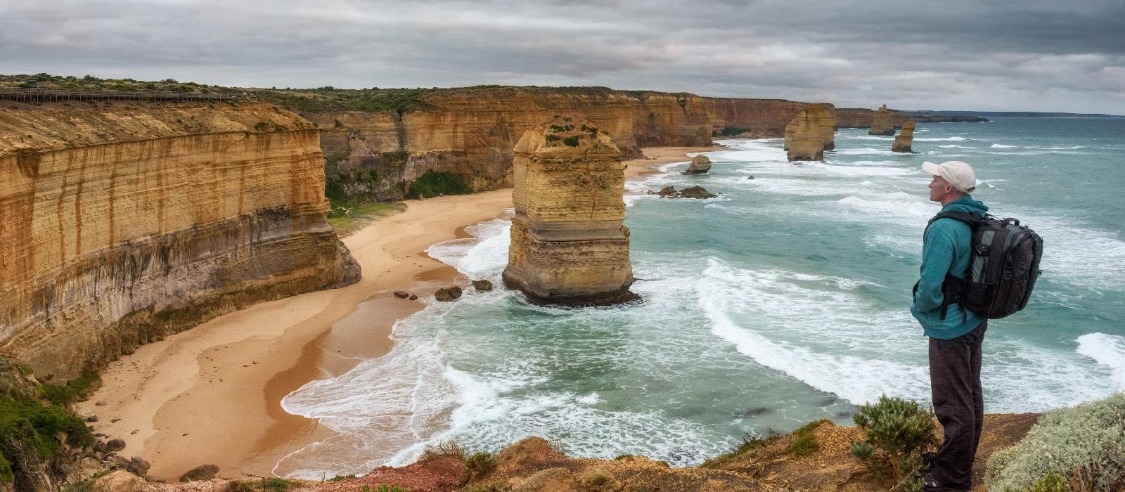 Wanderer mit Rucksack steht an den Klippen der Twelve Apostles an der Great Ocean Road in Victoria, Australien