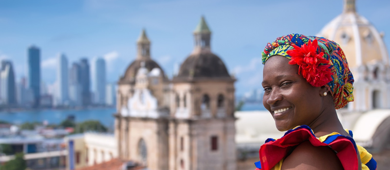 Woman in traditional costume against the backdrop of Cartagena de Indias