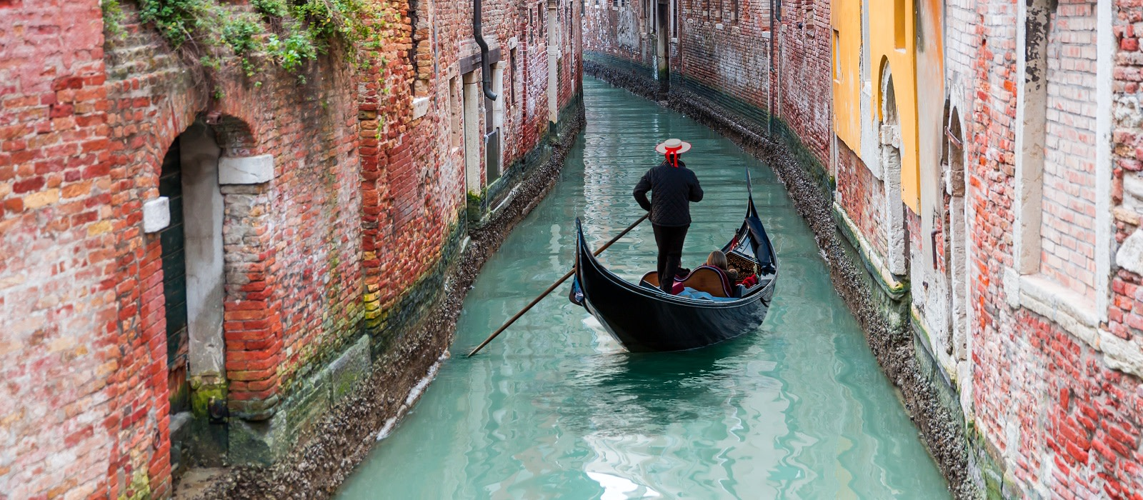 Enchanting Travels Italy Tours Venetian gondolier punting gondola through green canal waters of Venice Italy