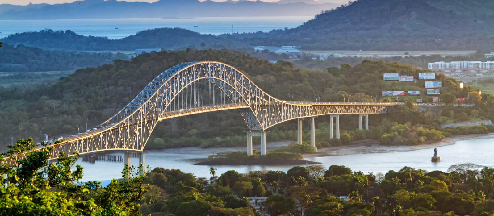 Panoramic aerial view of the Bridge of The Americas over the Panama Canal Pacific Entrance. Sunset scene with a gentle mist in the background. The bridge is spanning two continents - two Americas.