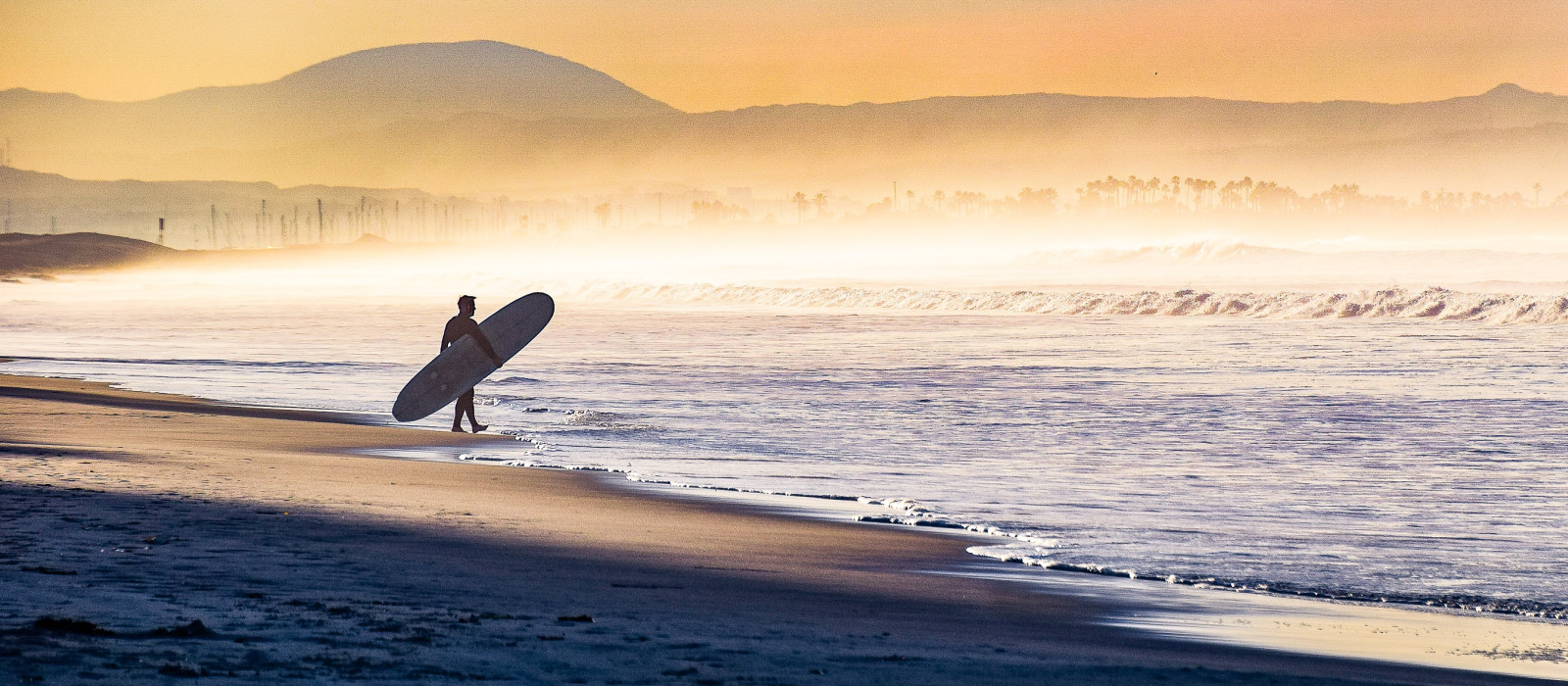 Early morning fog shrouds the coastline as this surfer enters the water in Coronado, California