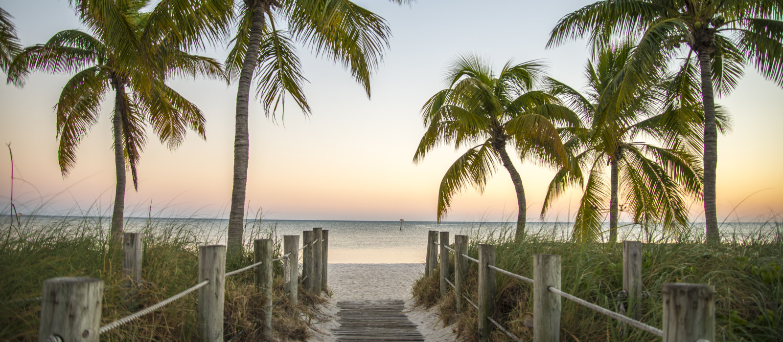 Key West Florida - Famous passage to the beach with palms, sunset and view on the ocean.