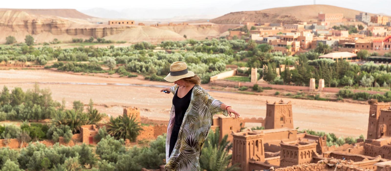 Eine  Reisende mit Hut, steht auf einer hohen Mauer mit ausgestreckten Armen, im Hintergrund der Stadt in der Wüste von Ait BenHaddou, Marokko, Afrika
