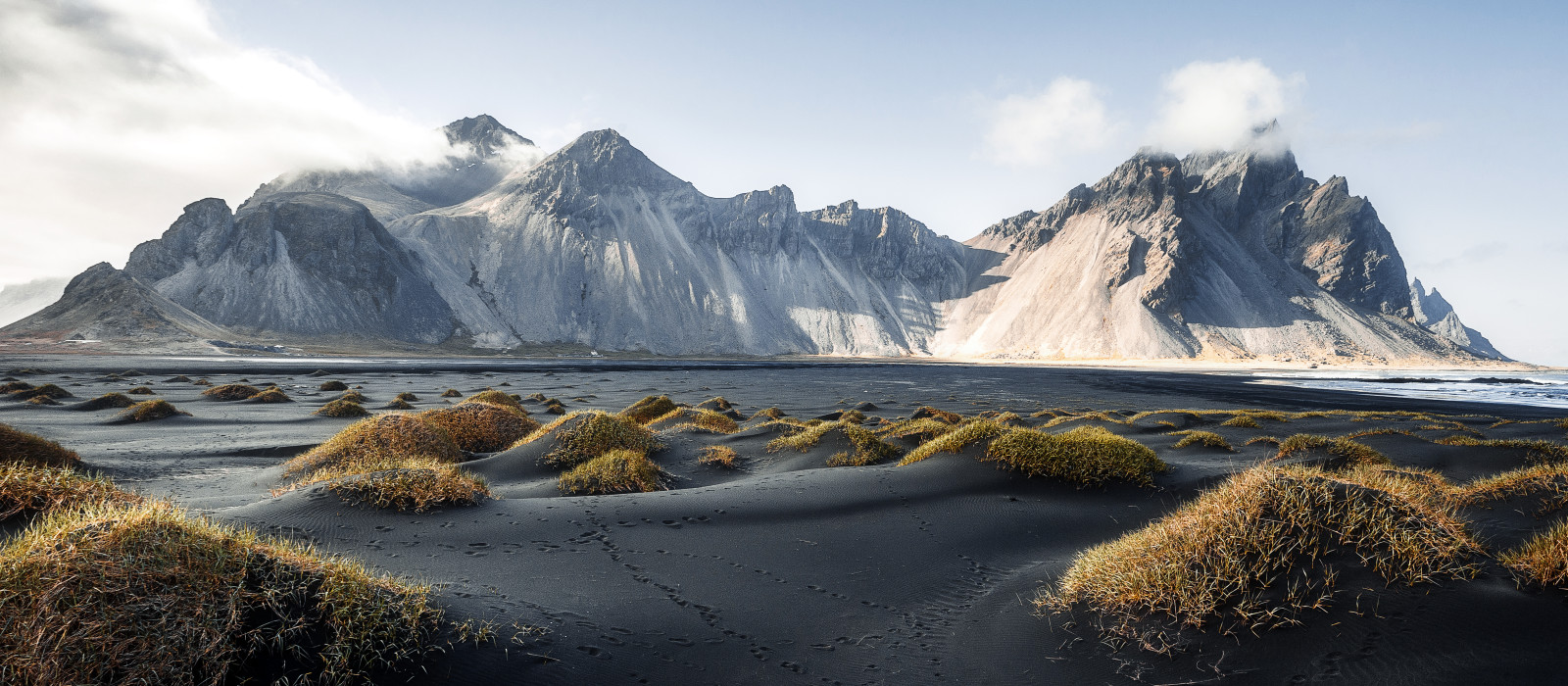 Gorgeous view on Stokksnes cape and Vestrahorn Mountain with black sand with grass on foreground at summer.