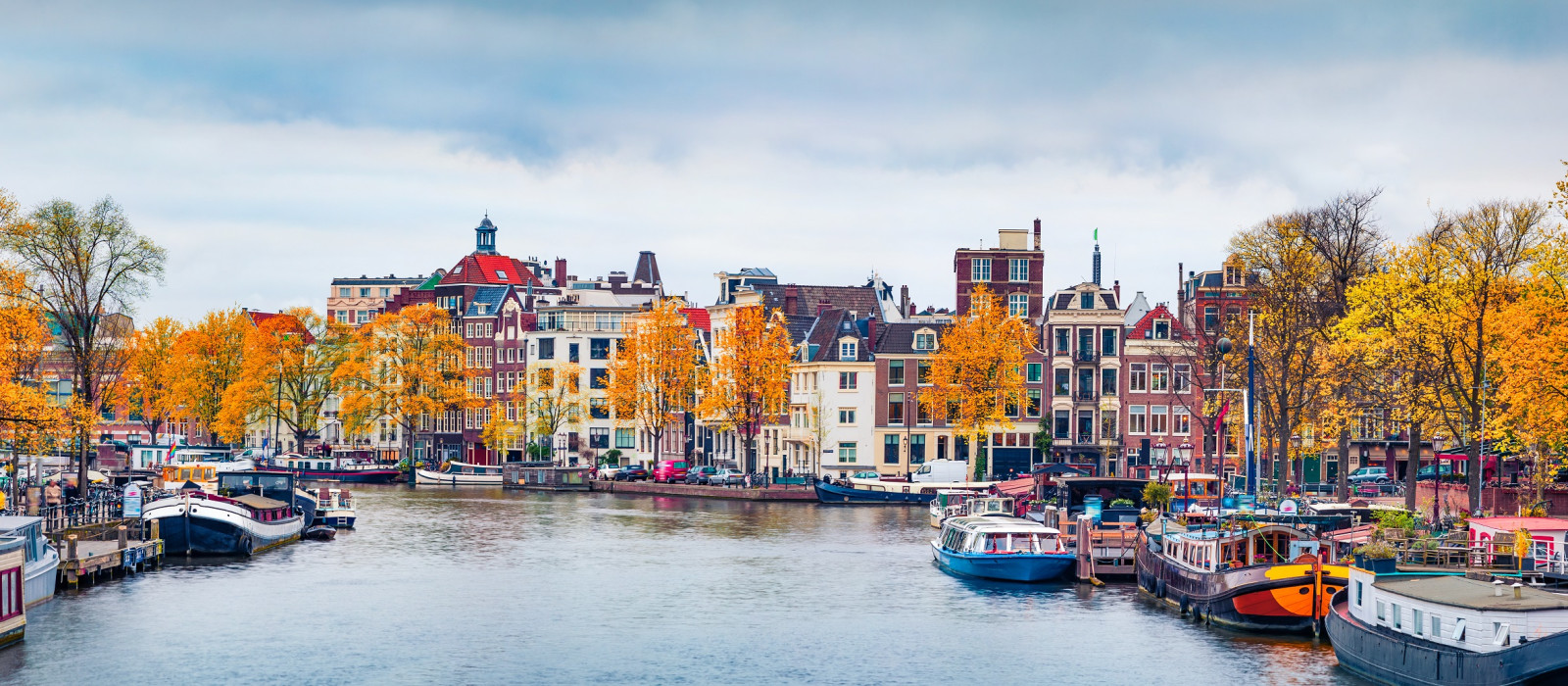 Panoramic autumn view of Amsterdam city. Famous Dutch channels and great cityscape. Gloomy morning scene of Netherlands, Europe. Traveling concept background. European Cities tours