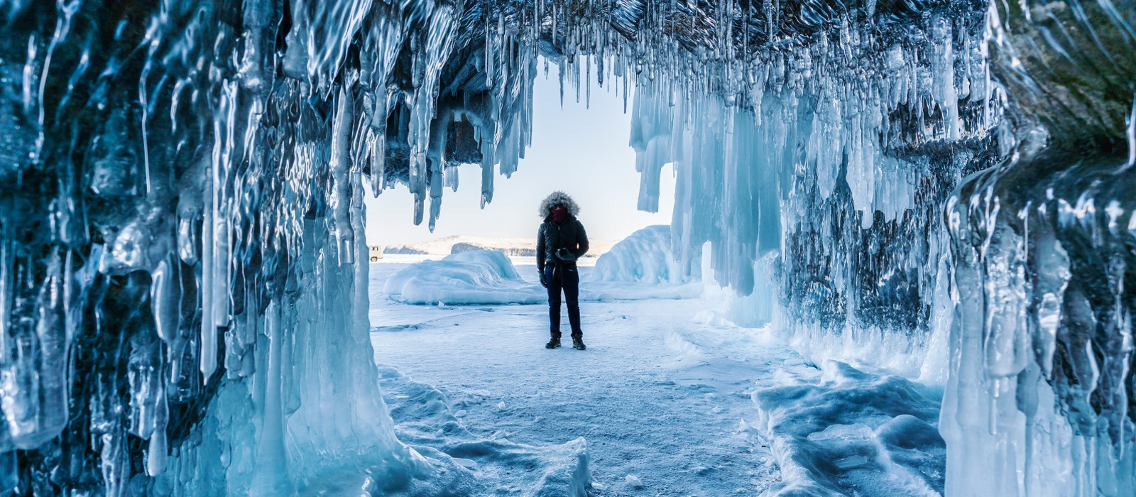Ein Mann steht auf dem gefrorenen Baikalsee mit Eishöhle in Irkutsk Sibirien, Russland