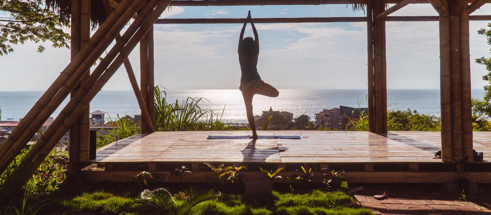 Frau praktiziert Yoga im Bambusstudio, Ecolodge-Retreat in Montanita, Ecuador, Südamerika