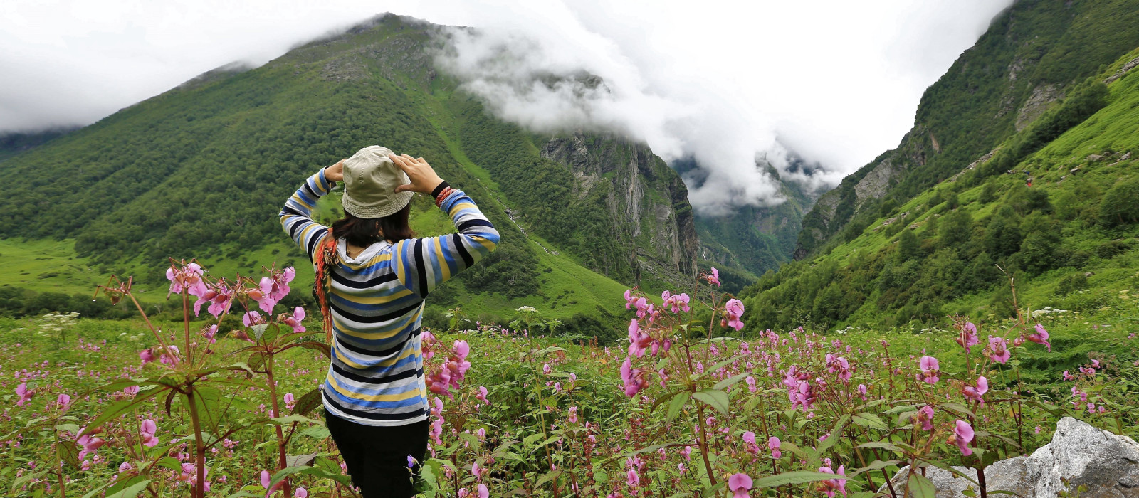 Young female climber walking down grassy rocky hill in green beautiful mountains in india