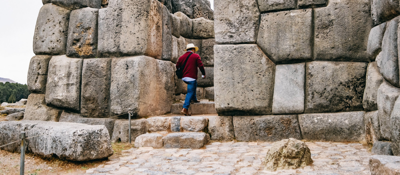 Man entering in front of the huge rocks of Sacsayhuaman in Cusco - Peru, South America