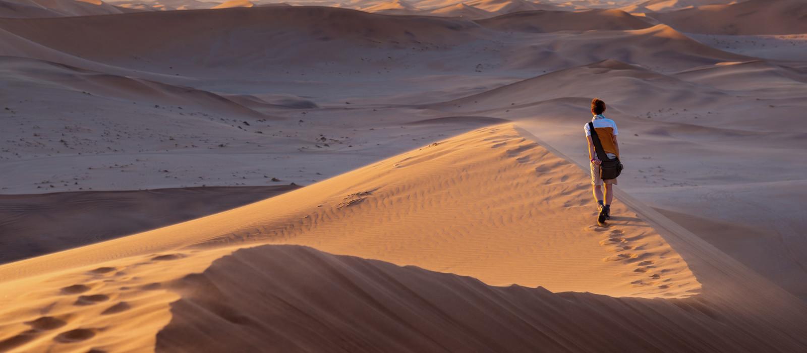 Tourist walking on the scenic dunes of Sossusvlei, Namib desert, Namib Naukluft National Park, Namibia, Africa
