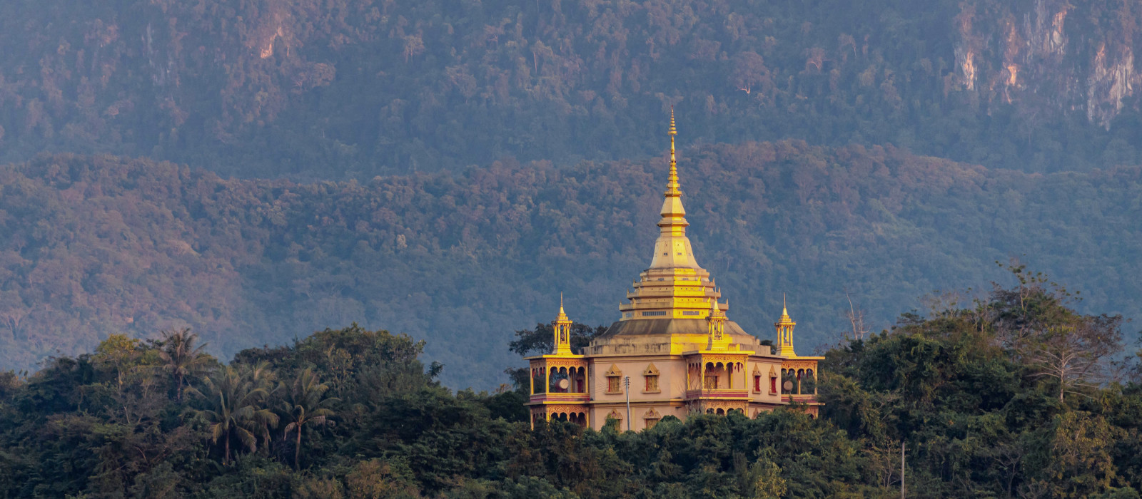 Beautiful Buddhist temple on the hill around with forest and big mountain background, Wat Pa Phon Phao at Luang Prabang, Laos, Asia