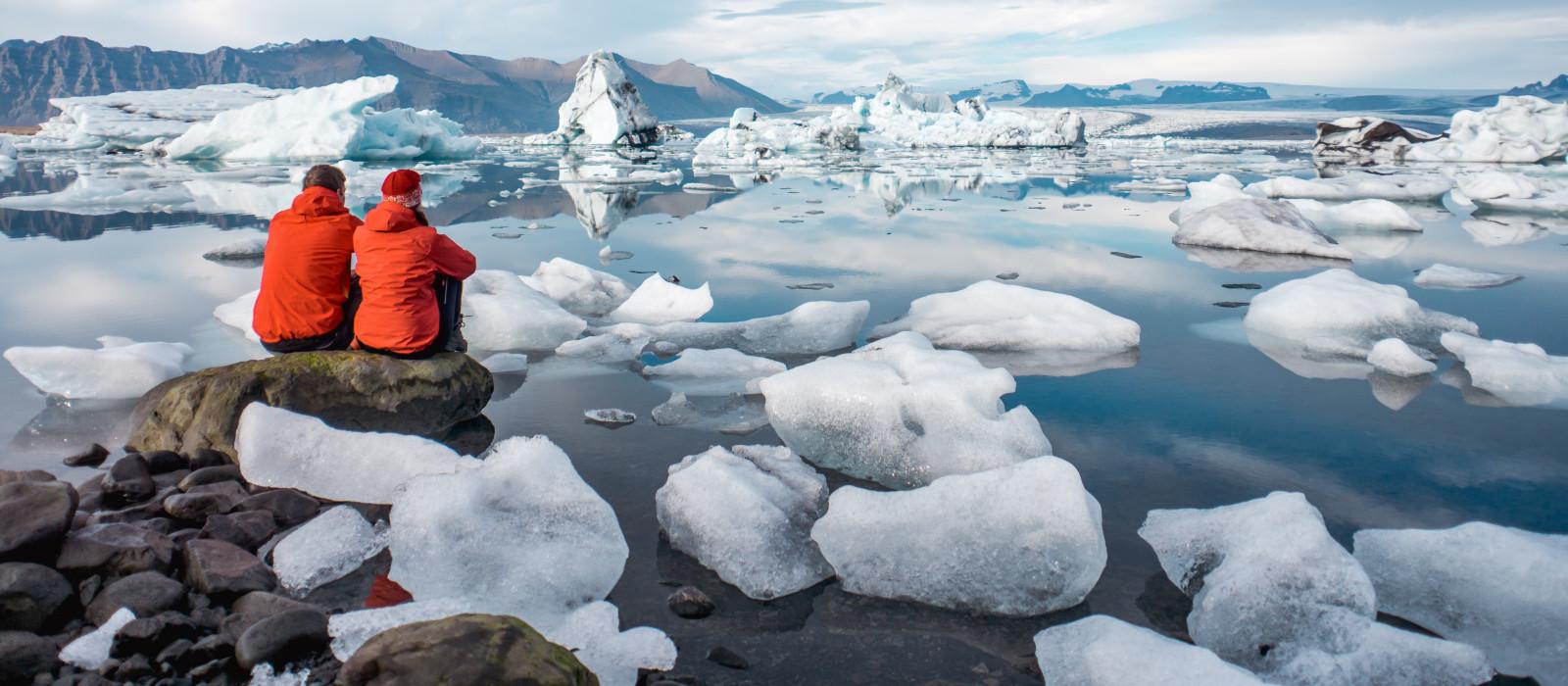 Junges Paar mit Blick auf die Gletscherlagune in Island