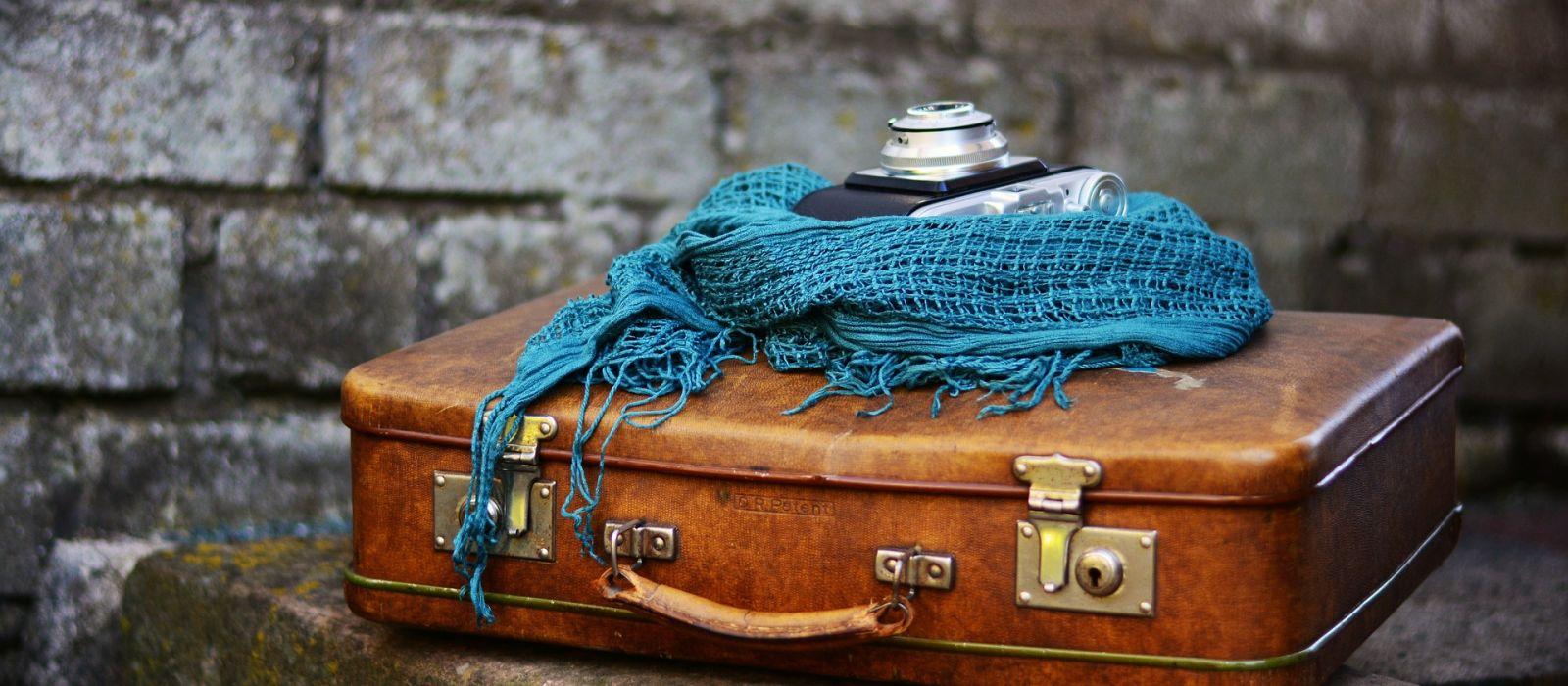 Stimmungsfoto von gepacktem Koffer mit Schal und Fotokamera