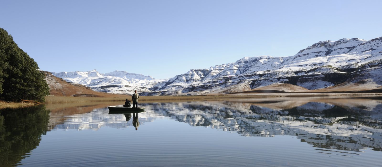 flyfishing for trout against a backdrop of snow at giants cup wilderness reserve, kwazulu natal, south africa - history of South Africa