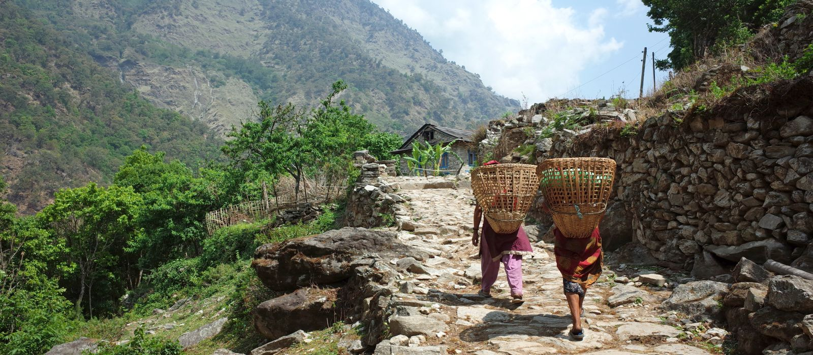 Nepalesische Frauen tragen Körbe auf traditionelle Weise im Himalaya, Region Solukhumbu, Nepal, Asien.