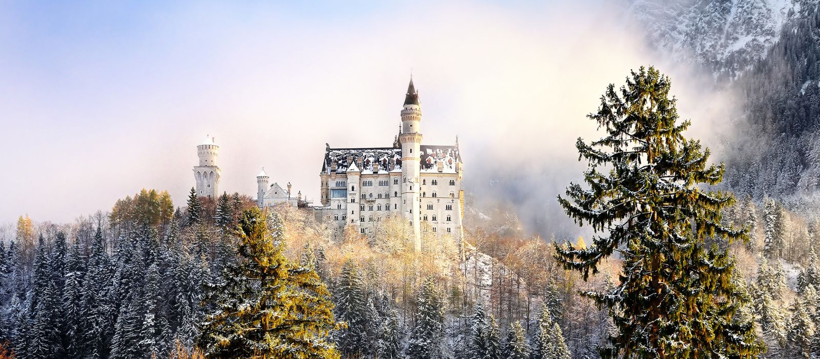 Splendid scene of royal castle Neuschwanstein and surrounding area in Bavaria, Germany (Deutschland). Famous Bavarian destination sign at sunny snowy winter day