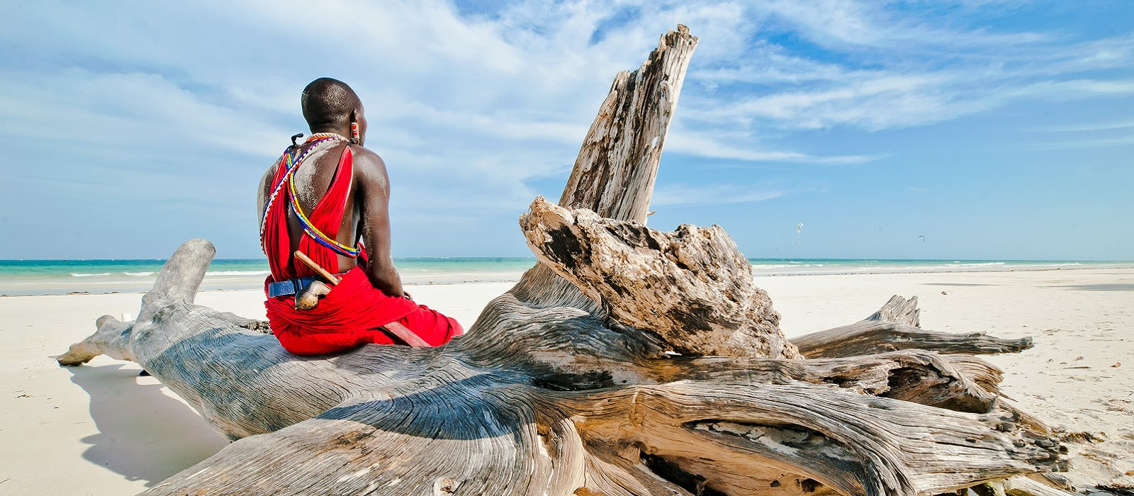 Enchanting Travels Tanzania Tours Man from the Maasai tribe sits on the shore of the Indian ocean - culture of Tanzania
