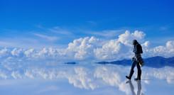 Girl on surface of salt lake Salar de Uyuni in Bolivia with sky reflection, South America