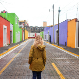 Girl walking up colorful colonial street in Cholula, Mexico