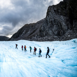 Hikers and travelers walking on ice in Fox Glacier