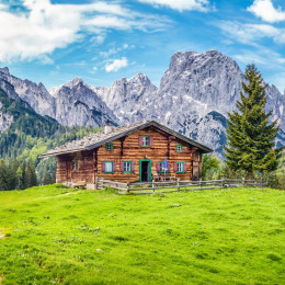 Panoramic view of beautiful mountain scenery in the Alps with traditional rural mountain chalet and fresh green meadows