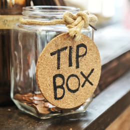 Germany Tour Vintage retro glass jar with hemp rope tie tip box tag and few coins inside on wood counter