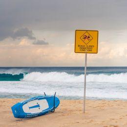 Warnschild mit der Aufschrift 'Beach closed, dangerous conditions' am Strand von Australien
