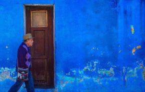 Alter Mann läuft an intensivblauer Häuserwand vorbei